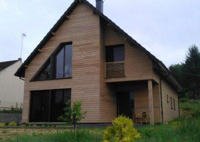 Maison en bardage mélèze et menuiseries gris anthracite.