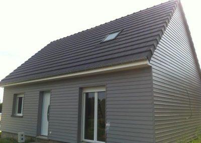 Maison en bardage bois et toiture en tuiles HP10 ardoisées, menuiseries PVC blanc